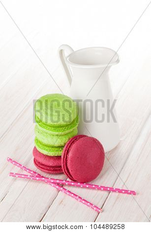 Colorful macarons and milk jug on white wooden table