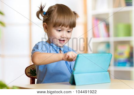 child girl playing with a digital tablet at home
