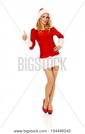 Woman in santa clothes gesturing thumbs up.