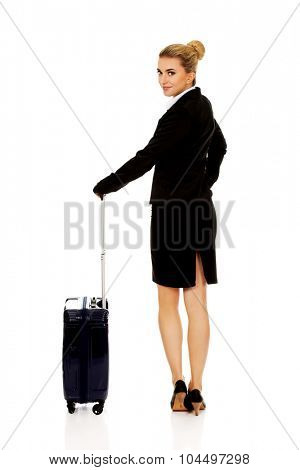 Smile businesswoman dragging wheeled suitcase.