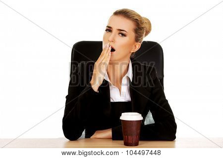 Yawning businesswoman drinking coffee from paper cup behind the desk.