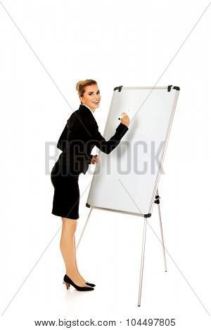 Smiling business woman writing on flipchart.