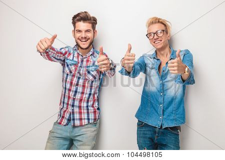 two happy young casual men making the ok thumbs up hand gesture in studio