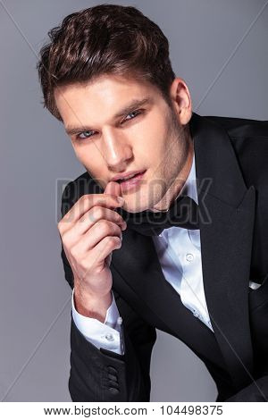 Portrait of a handsome business man holding his thumb near his mouth.