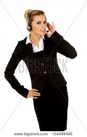 Young woman helpline operator is trying to hear something headphones.