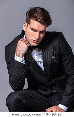 Elegant young business man looking down while fixing his ollar.