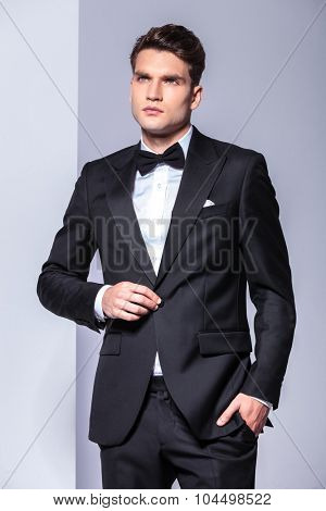Business man holding one hand in his pocket while unbuttoning his tuxedo, looking up.