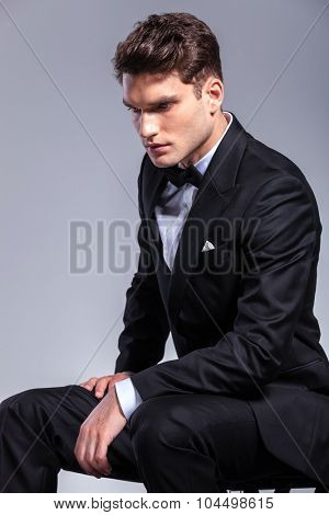 Side view of a young elegant business man looking down while sitting.