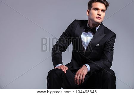 Young elegant business man sitting while looking up.