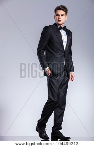 Side view of a young business man walking with his hand in pocket on studio background.
