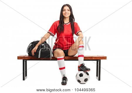 Young female soccer player sitting on a wooden bench with a sports bag beside her isolated on white background