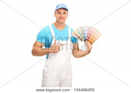Studio shot of a young male painter holding a color swatch and pointing towards it with his finger isolated on white background