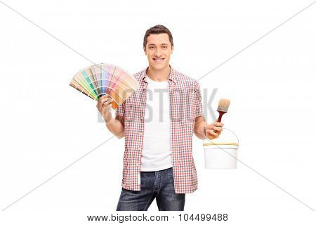 Studio shot of a cheerful young man holding a color swatch and a paintbrush isolated on white background