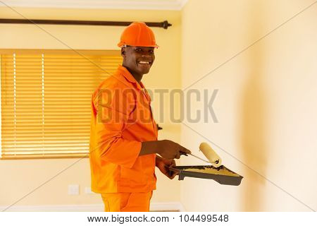 happy african contractor painting inside the house