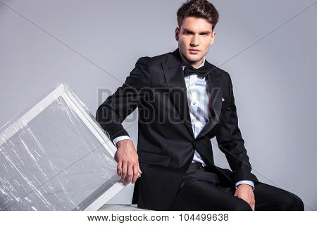 Business man sitting while leaning on a white table wrapped in plactic foil.