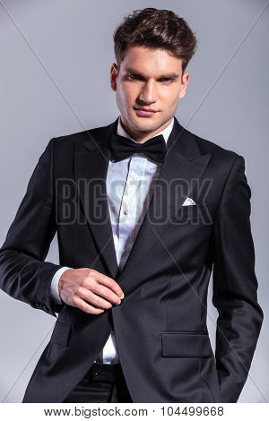 Young business man unbuttoning his tuxedo while smiling at the camera.