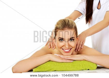Young smile beautiful woman lying on a massage table and has massage.