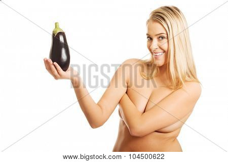 Shirtless smiling woman holding an aubergine.