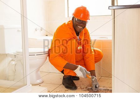 cheerful african american construction worker removing floor tiles in bathroom
