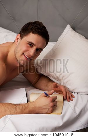 Handsome man learning to exam in his bedroom on bed.
