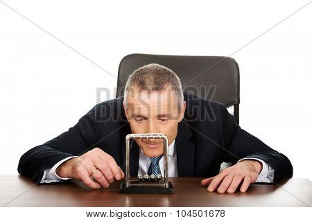 Mature businessman in office playing with newton balls.