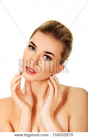 Young topless woman touching her face