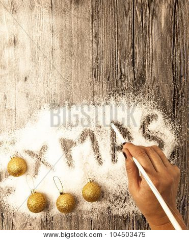 Christmas background with woman writing word Xmas on the snow on wooden backdrop. Gold balls and snow on wooden table.
