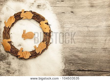 Christmas card with gold Christmas wreath and cute small rabbits from bark on winter snow and wooden background. Christmas banner with place for your text
