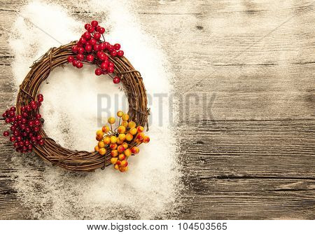 Christmas card with red and yellow Christmas  berries and wreath on wooden background with snow. Christmas banner with place for your text