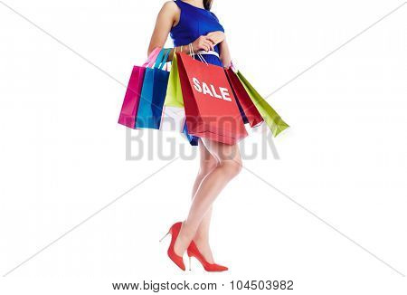 Young female in blue dress holding paperbags