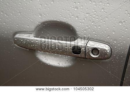 Door handle of a car in rain