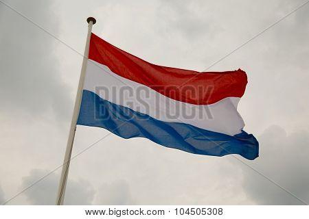 Dutch flag waving against cloudy sky