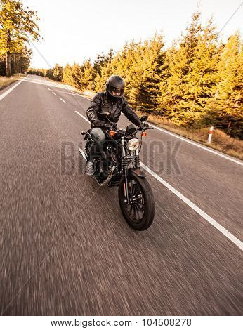 ROUSINOV - SEPTEMBER 29: Harley-Davidson Motorcycle Sportster Iron 883, drives through the forests during sunrise. September 29, 2015 in Rousinov, Czech republic.