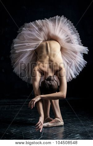 Beautiful ballerina  posing leaning on dack background