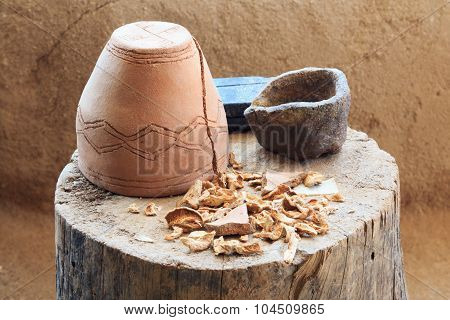 Inverted Ceramic Pot Standing On A Tree Stump With Dried Mushrooms