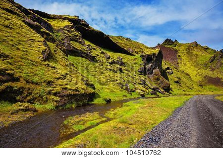 Canyon Pakgil in Iceland. Picturesque basalt hills covered with green grass and moss-polar. At the bottom of the canyon flowing streams lot