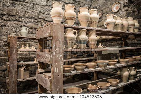 shelves with pottery in workshop
