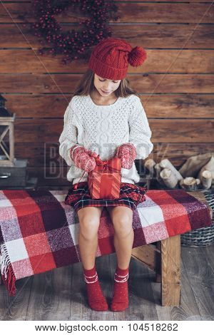 Child opens a Christmas present on rustic wooden background, farmhouse interior.