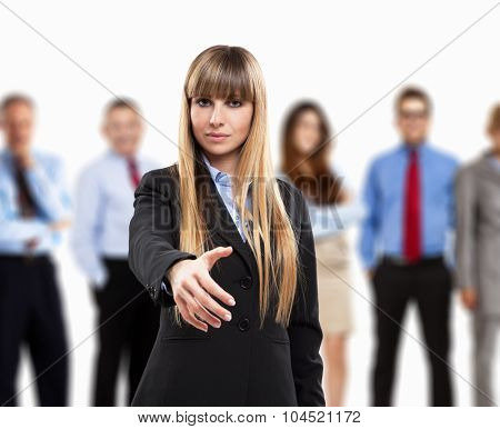 Business woman offering an handshake. Group of people in the background