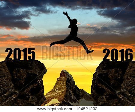 Girl jumps to the New Year 2016 at sunset. In the background Matterhorn - Pennine Alps, Switzerland.