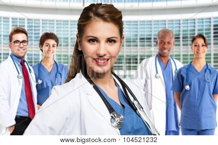 Portrait of a smiling young doctor in front of a group of medical workers