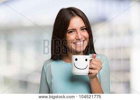 Smiling and cheerful woman holding a smiling cup