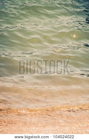 closeup of lake water by the muddy beach