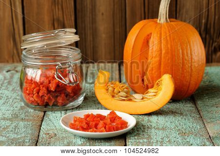 Homemade Candied Pumpkin Pieces In Glass Jar And White Plate With Cut Pumpkin With Seeds On Old Wood