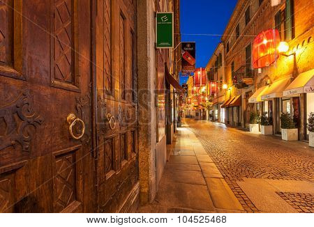 ALBA, ITALY - DECEMBER 30, 2014: Wooden door and illuminated pedestrian street with shops at Christmas time. This area is popular with locals and tourists visiting Alba for winter holidays.