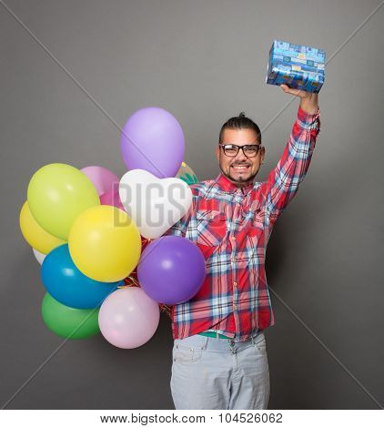 Handsome hipster man with baloons and a present in studio