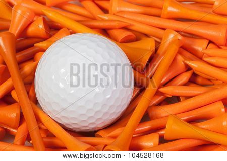 White Golf Ball Lying Between Wooden Tees