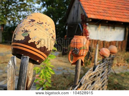 Traditional Ukrainian clay jugs on wooden fence