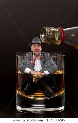 Alcohol addiction concept - man inside a cocktail glass