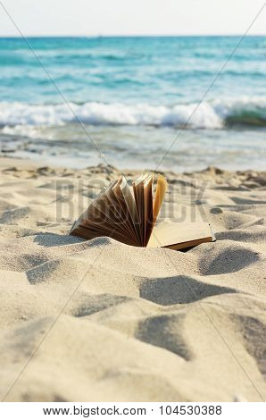 An open book laying on a sandy beach.